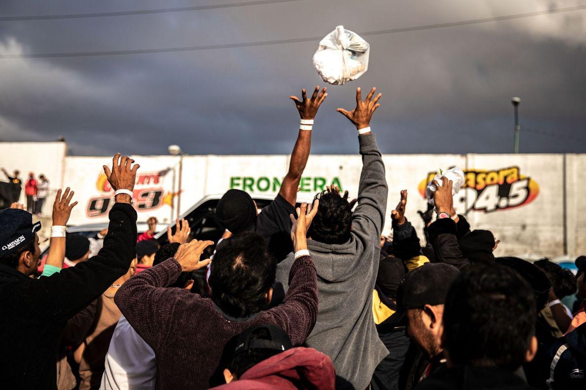 Un grupo de caridad arroja bolsas de productos de higiene a una multitud en el refugio. ...