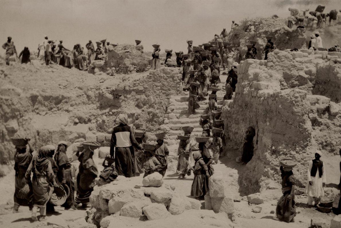 Las mujeres transportan montones de tierra lejos de las ruinas del palacio de Acab en Samaria ...