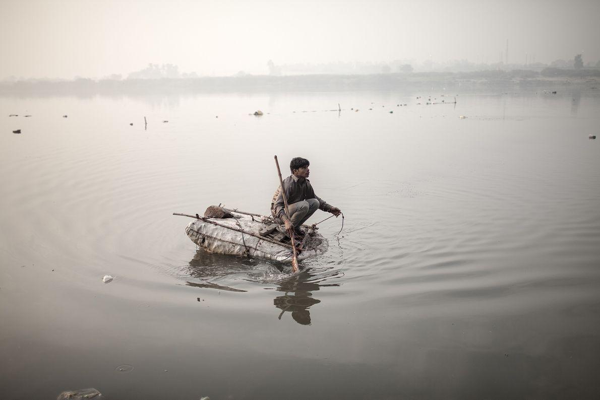 Un niño vagabundo intenta pescar monedas con una cuerda y un magneto en el río Yamuna ...