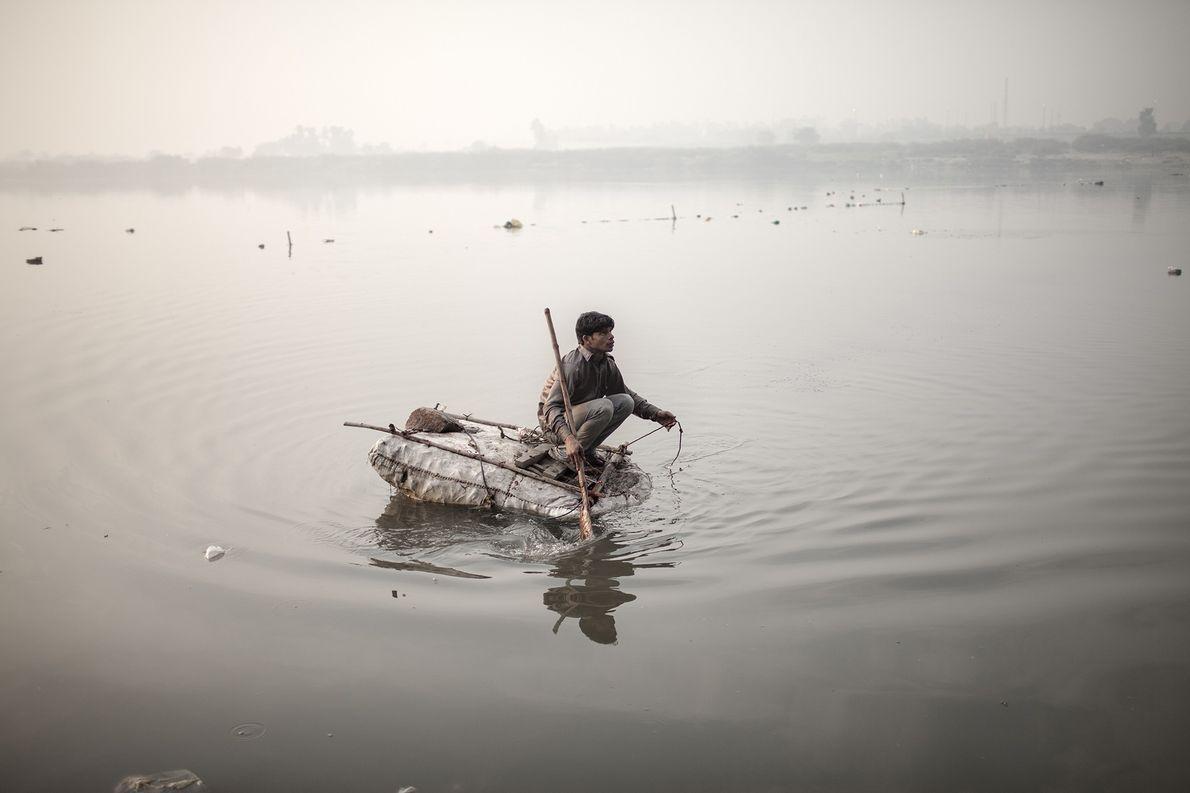 Un niño vagabundo intenta pescar monedas con una cuerda y un magneto en el río Yamuna …