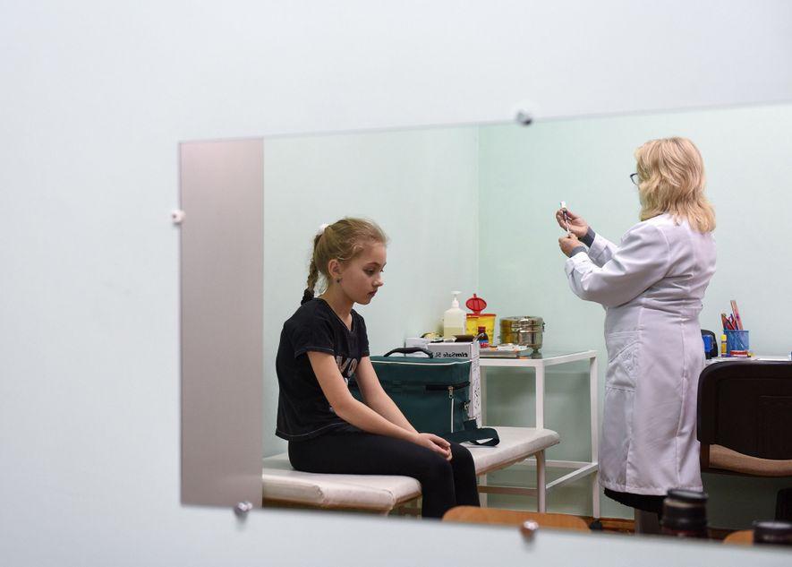 Una enfermera prepara una vacuna contra el sarampión en una escuela en el pueblo de Lapaivka, ...