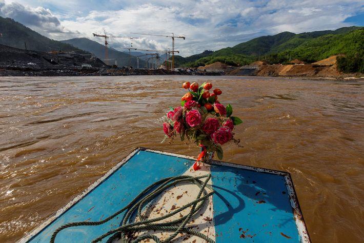 Un bote adornado con flores artificiales se dirige al sitio de construcción de la represa Xayaburi. ...