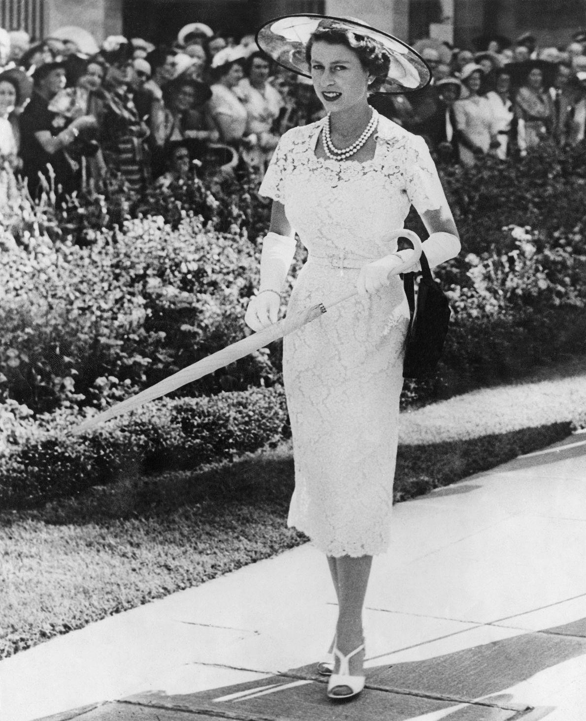 Luciendo un vestido blanco de encaje y un sombrero de ala ancha, Su Majestad saluda a ...