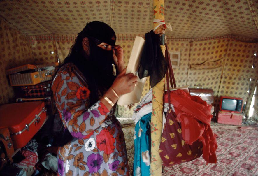 Una mujer beduina se ajusta el velo en una tienda de campaña en Wadi Nisah en ...