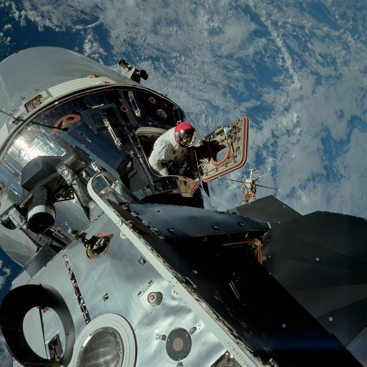 El astronauta Dave Scott asoma la cabeza desde el módulo de comando del Apolo 9, mientras …