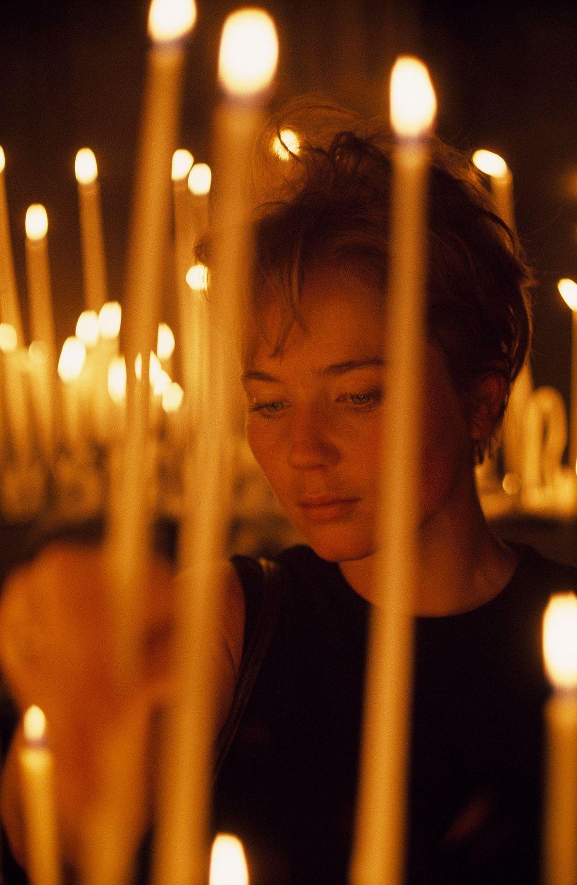 Un turista estadounidense enciende una vela en la catedral en 1968.