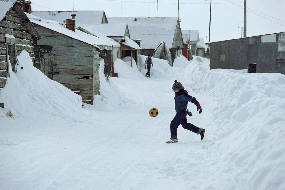 Un niño patea una pelota de fútbol en una calle nevada en Barrow, Alaska.