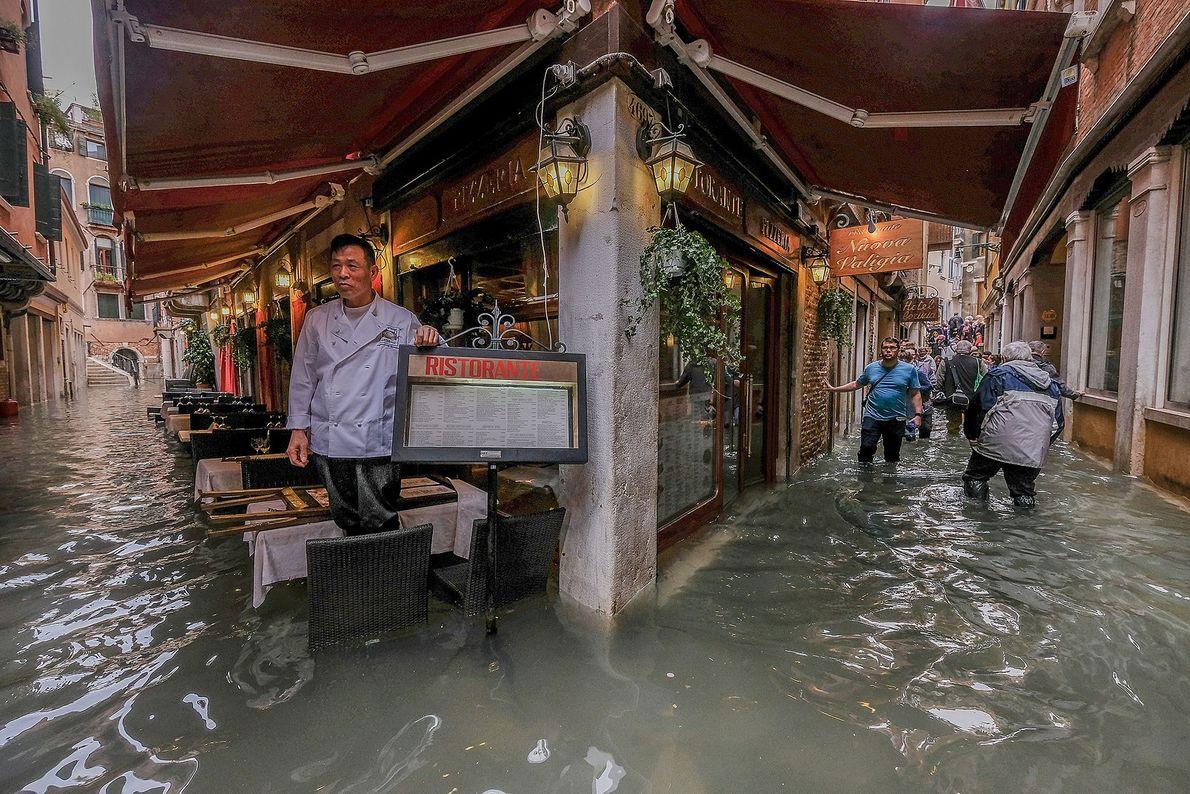 El dueño de un restaurante examina la marea alta.