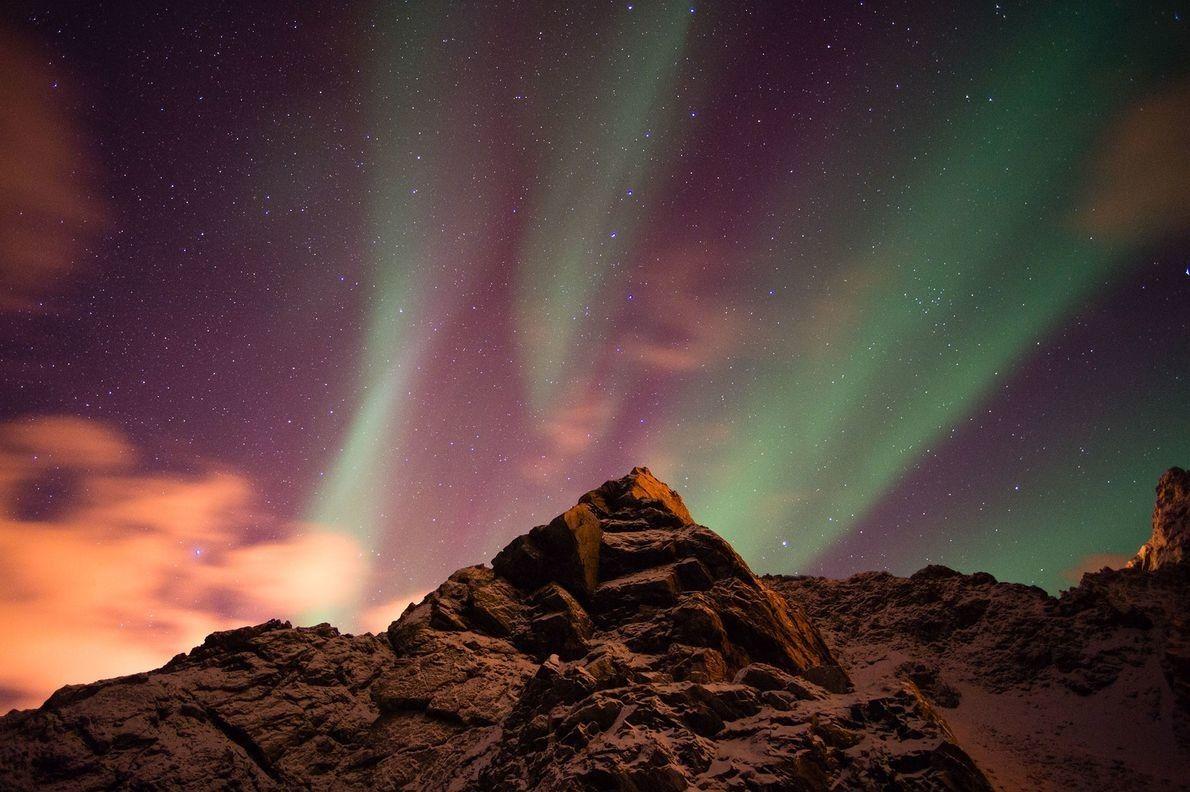 El pico de una montaña sobresale entre las auroras boreales del archipiélago Vesterålen, en Noruega.