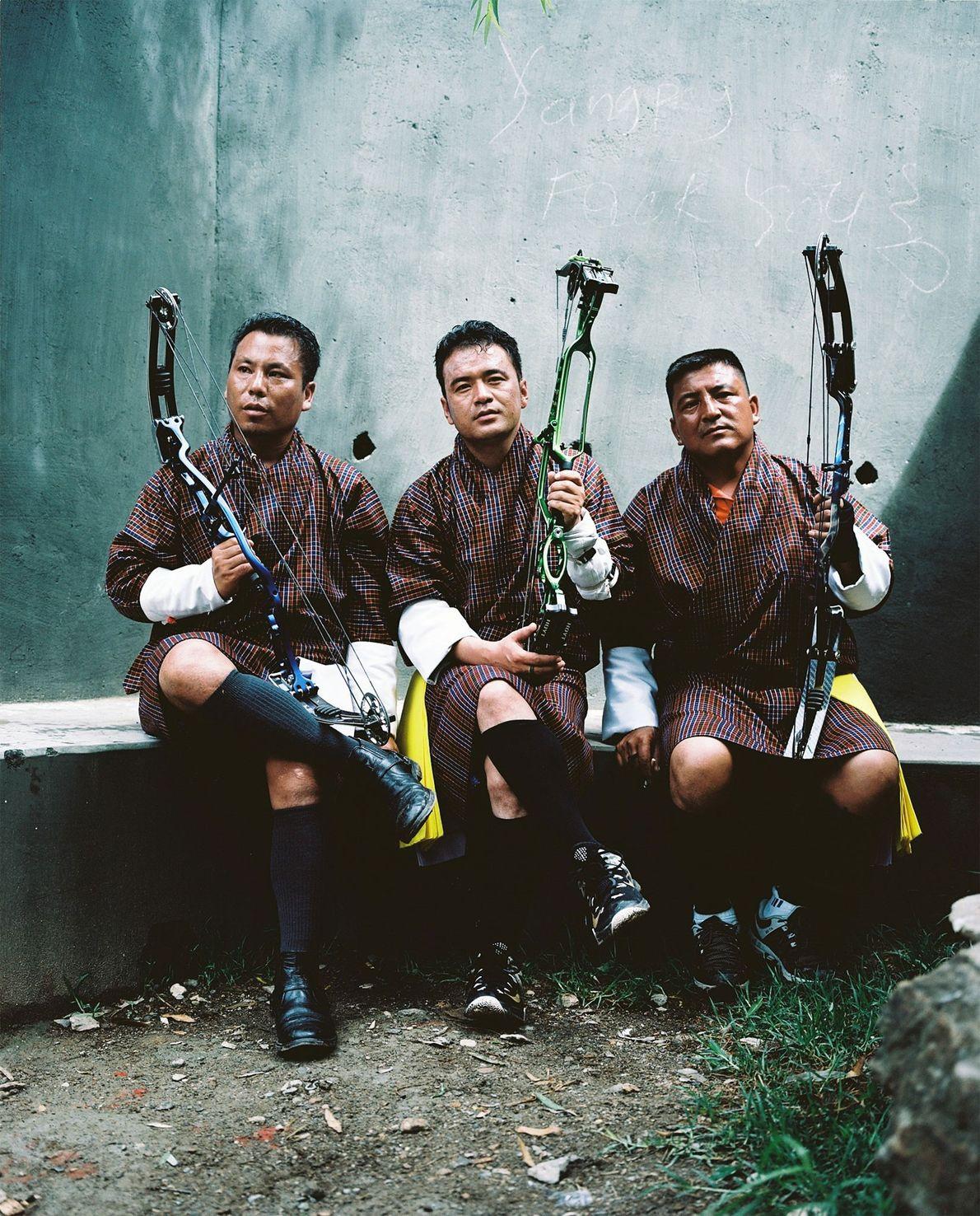 Tres hombres descansan durante una competición local de tiro con arco en Paro. De izquierda a ...