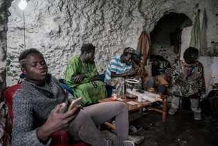 Los inmigrantes senegaleses se sientan dentro de una cueva en la parte superior de las colinas. ...