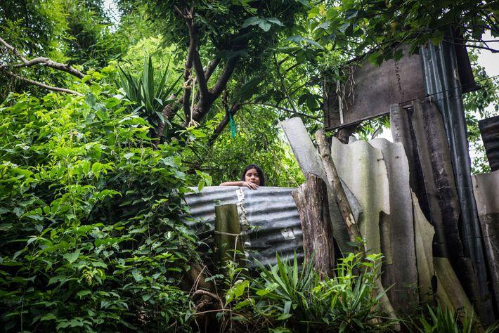 Una mujer mira por encima del muro provisional frente a su casa en el vecindario de ...