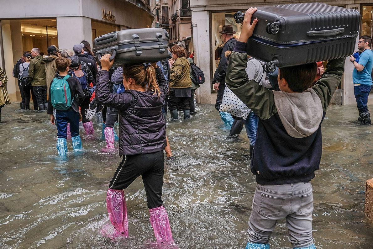 La gente lleva su equipaje sobre sus cabezas para mantenerlo lo más seco posible.