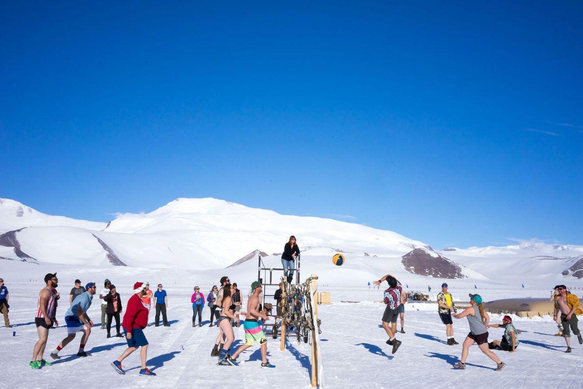 El personal del campamento, los científicos y los pilotos juegan al voleibol en el campamento de ...