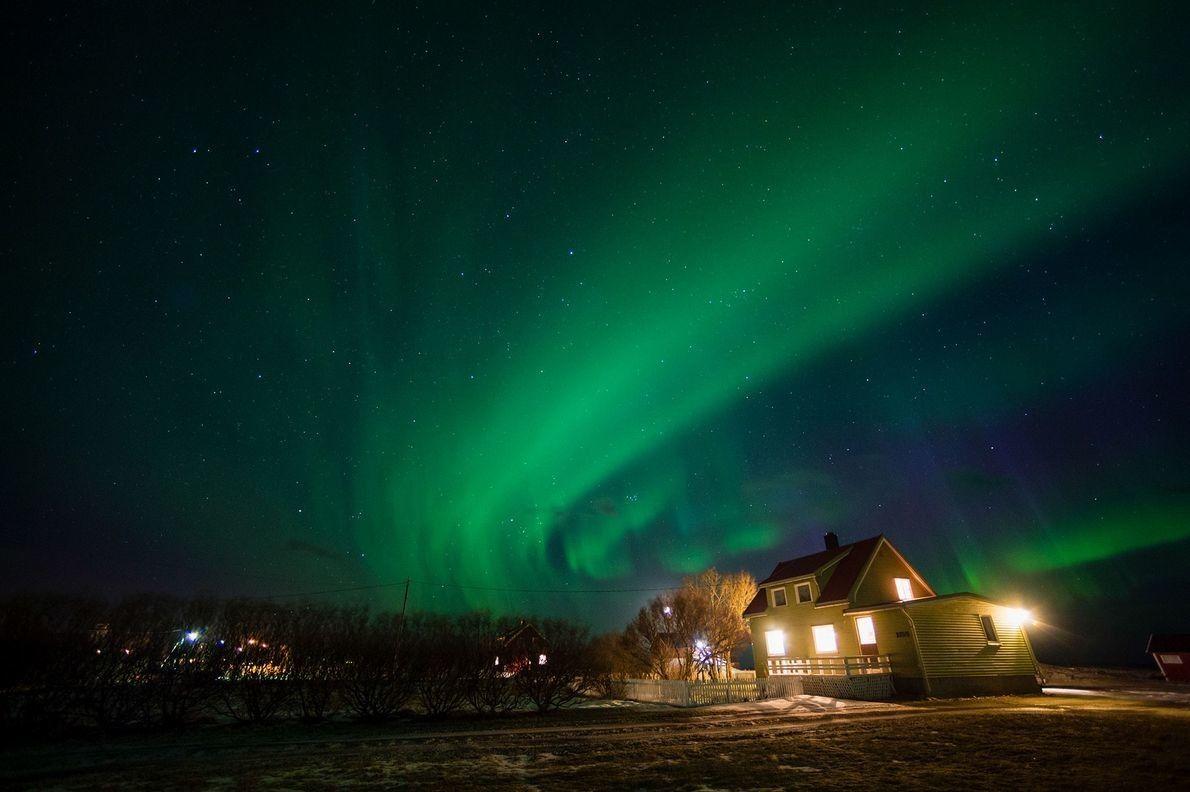 Las auroras fluyen sobre una casa en Nordland, Noruega.