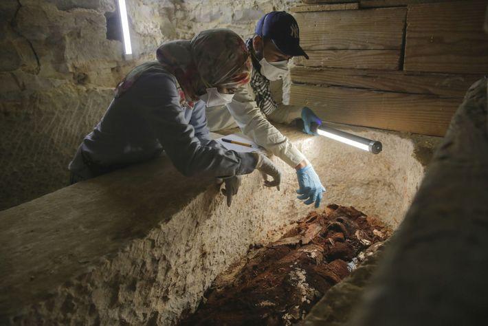 Los arqueólogos Maysa Rabeeh (izq.) y Mohammed Refaat (dcha.) examinan el ataúd de madera deteriorado de ...