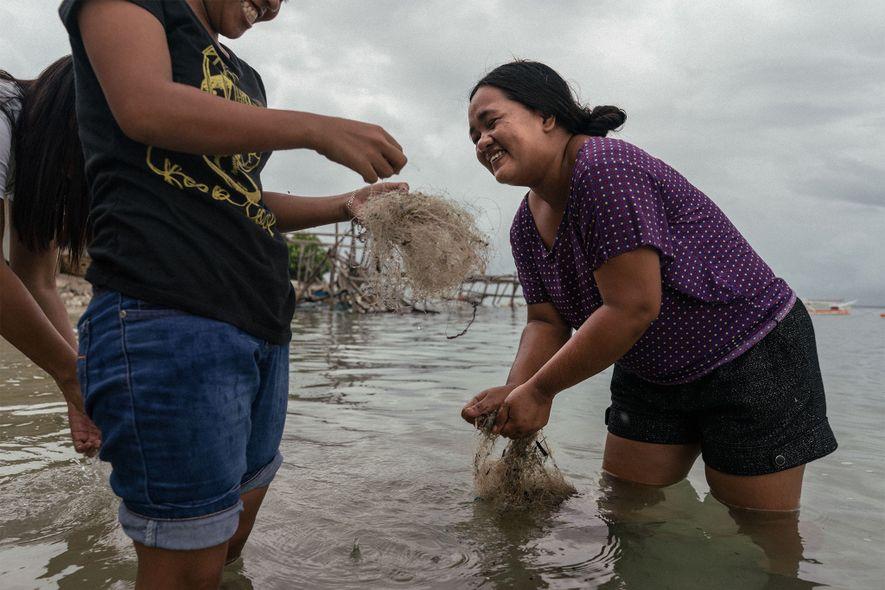 Mujeres filipinas limpian redes descartadas para venderlas y reciclarlas en el extranjero.