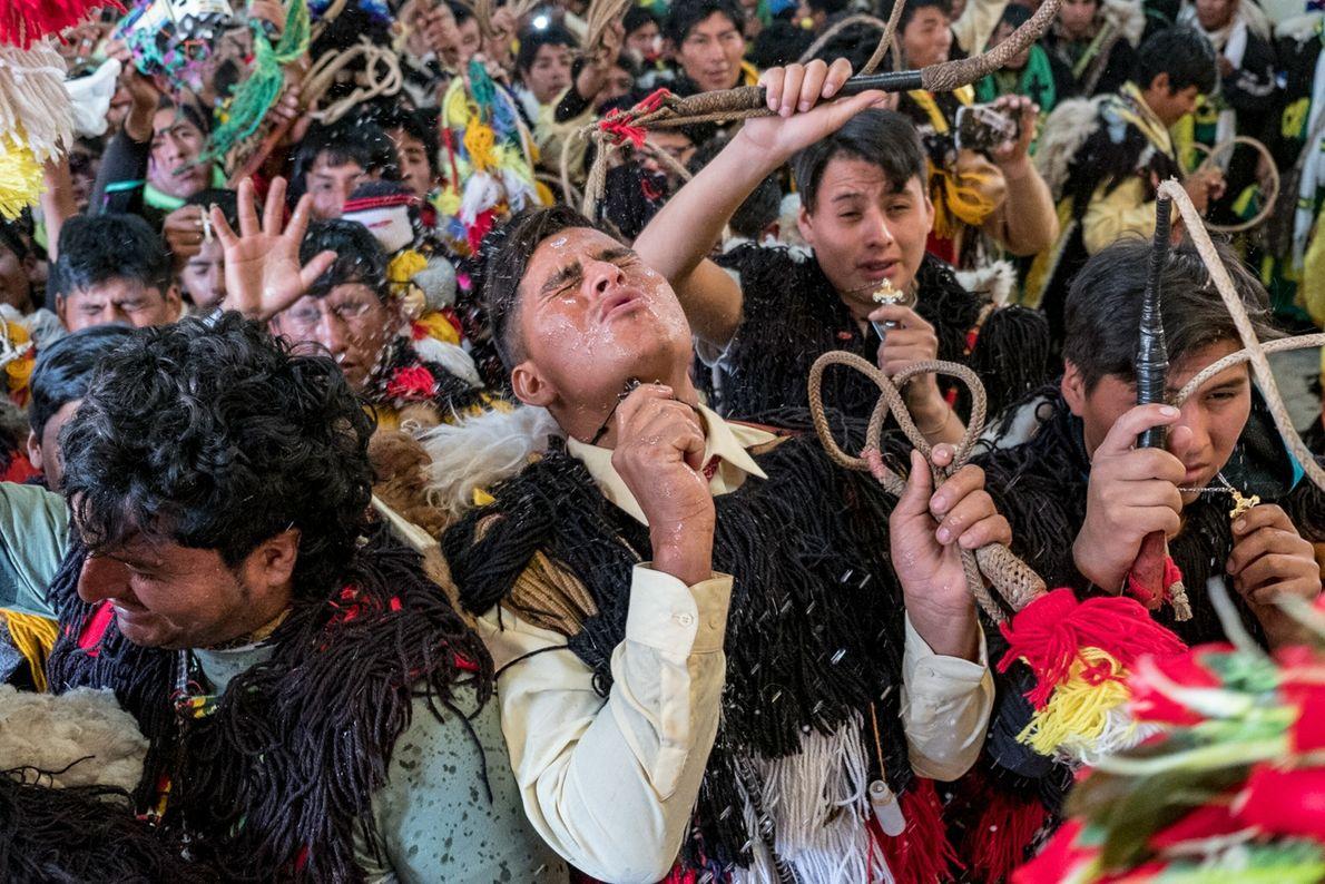 Un danzante de la nación Paruro es bendecido con agua bendita durante una misa en el ...