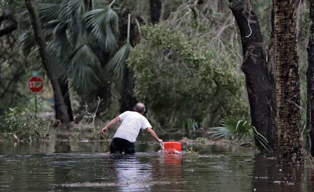 Un residente de St. Marks, Florida, saca un refrigerador portátil de las aguas inundadas cerca de ...