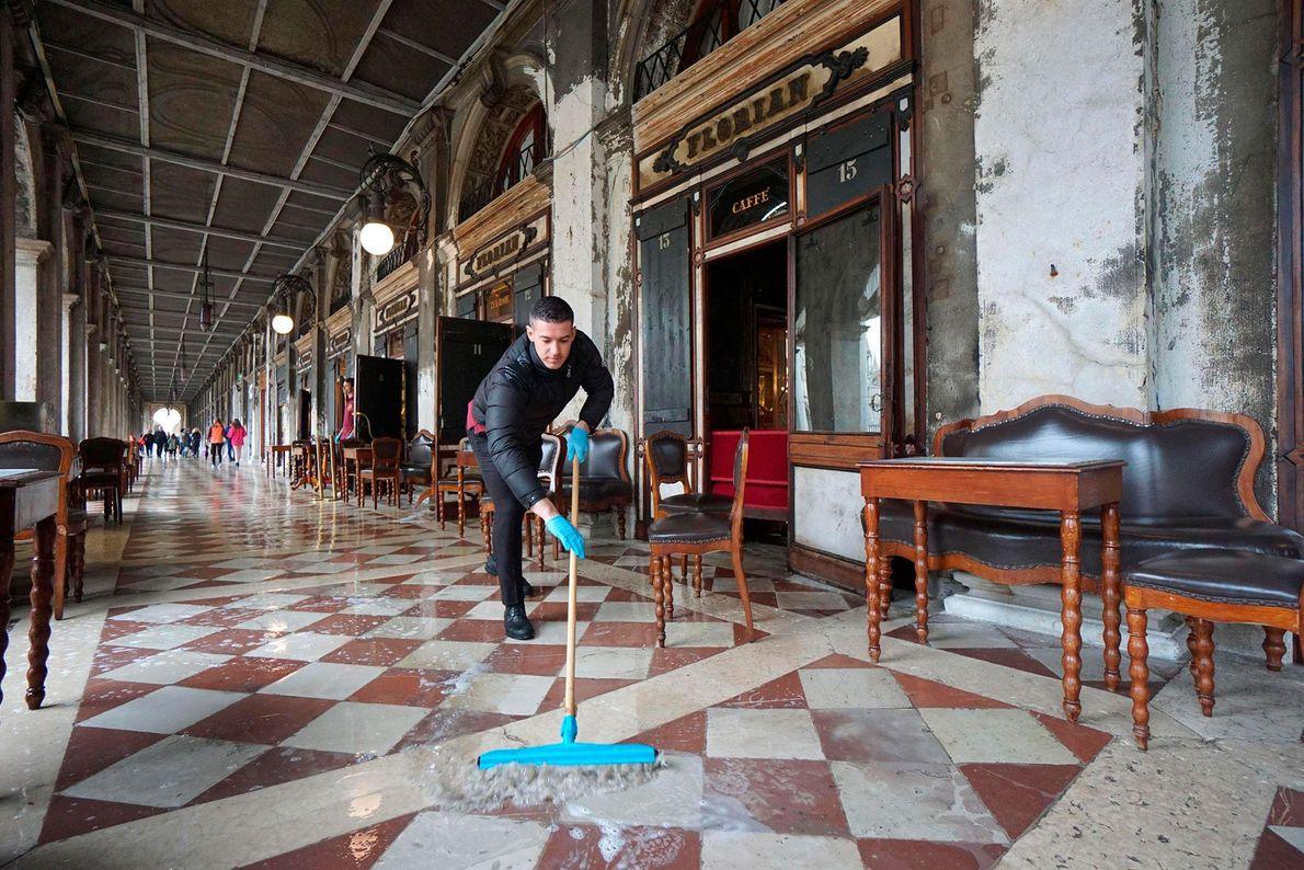Un hombre limpia el agua de la inundación en la vereda del histórico Caffe Florian, en ...