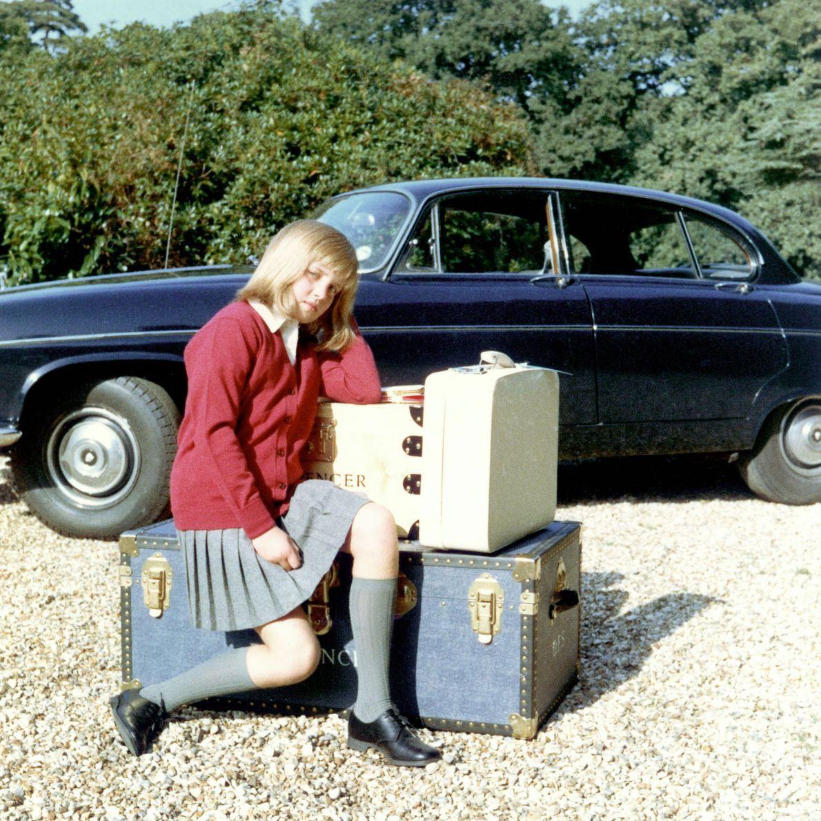 Diana sentada sobre sus maletas mientras se prepara para ir al internado en la escuela Riddlesworth ...