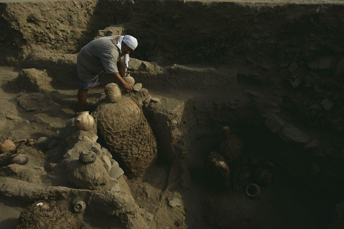 Un arqueólogo quita objetos cerca de un paquete de momias incas. Miles de los paquetes de ...