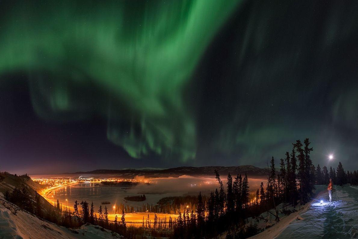 Un hombre contempla la aurora boreal sobre la ciudad de Whitehorse, en el territorio canadiense de ...