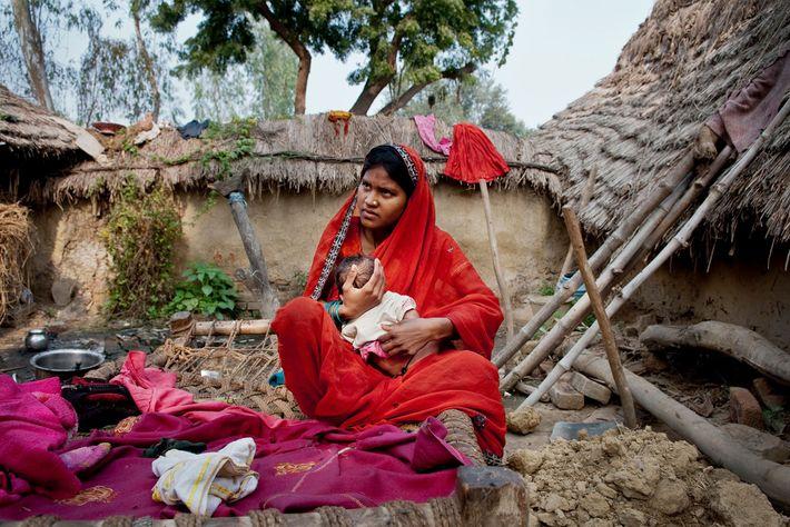 Phulmati, de 17 años, abraza a su hijo en su casa. La niña promedio de Shravasti ...