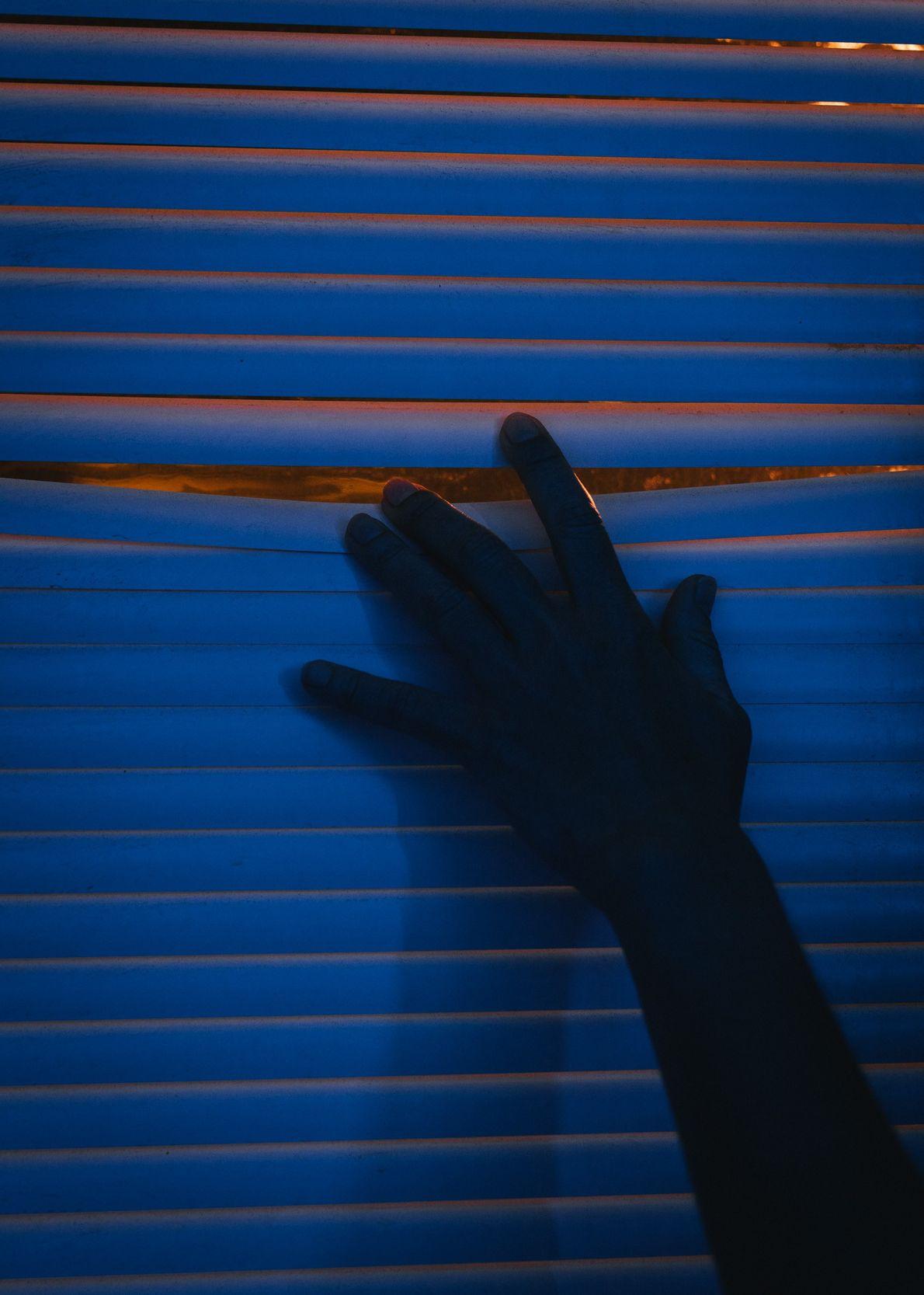 Aline Decadi, miembro de la tripulación de campo, se asoma por la persiana de una ventana ...