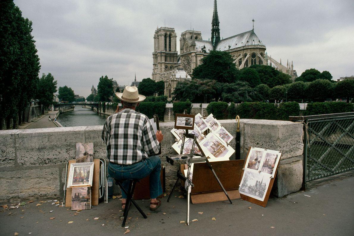 Un artista contempla a Notre Dame desde el Pont de L'Archeveche.