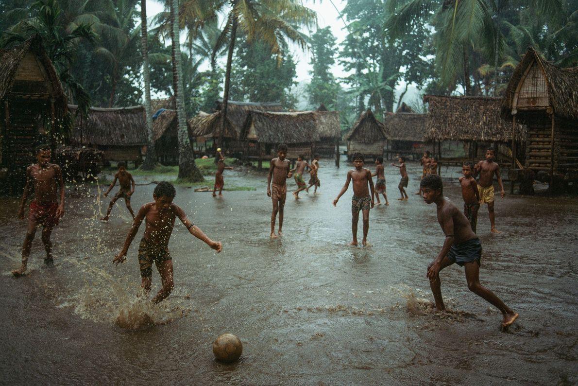 Niños juegan al fútbol en una aldea inundada en la isla Kiriwina, la más grande de ...