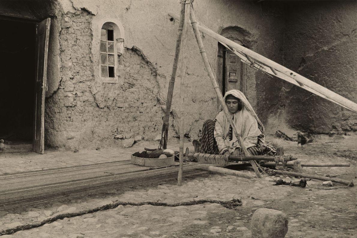 Una mujer de Kashkai hace una alfombra con su telar en Dehbid, Persia, en 1921.