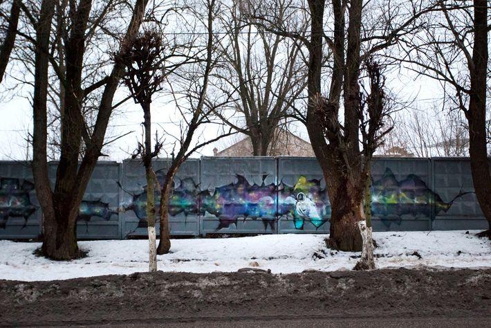Un grafiti de temática espacial decora una cerca de cemento en la calle Gagarin del pueblo ...