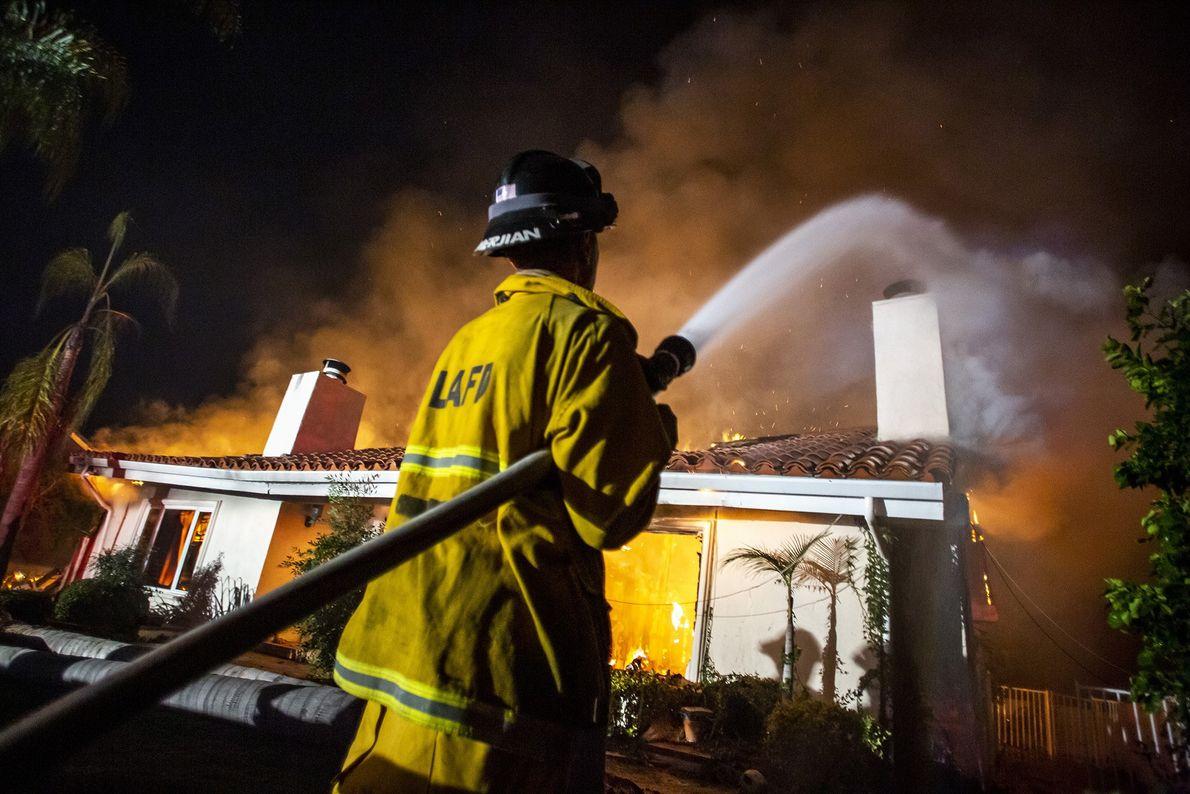 Los bomberos trabajan para controlar el incendio de una casa atrapada en el incendio de Woolsey ...