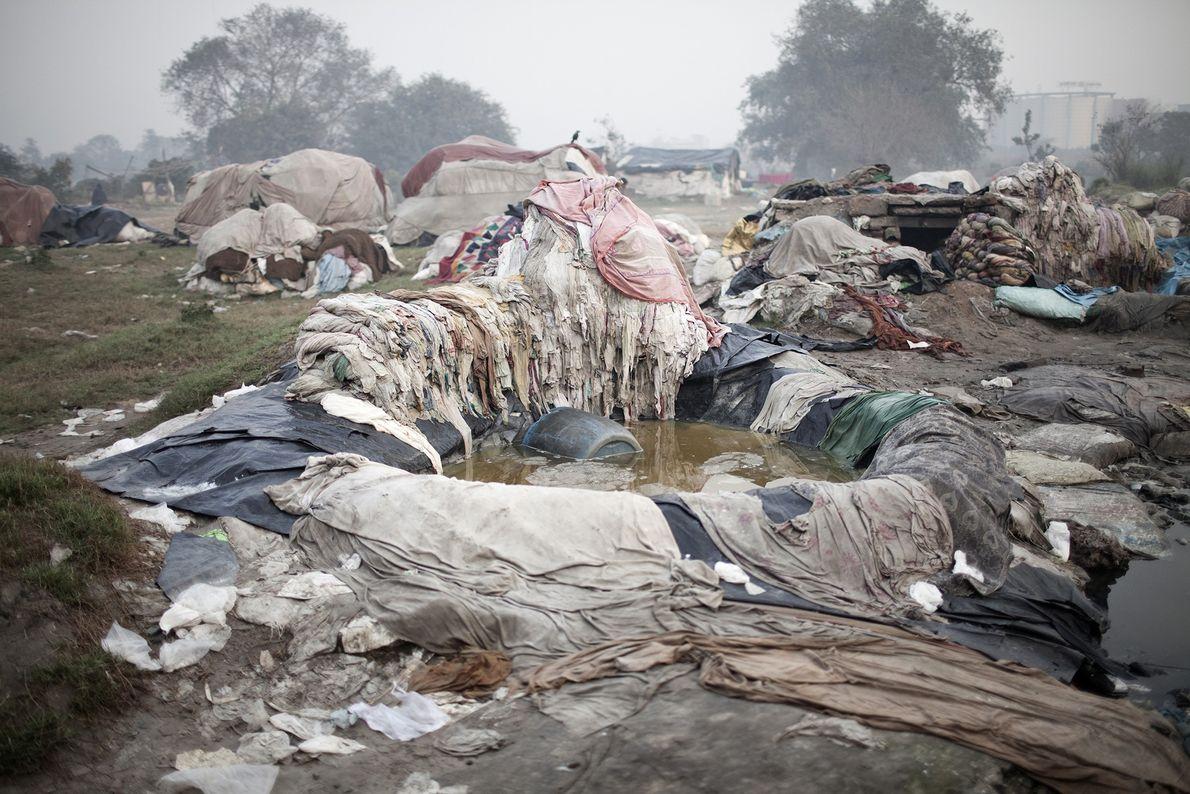 Pilas de ropa sucia de hoteles yacen en el barro en el río Yamuna.