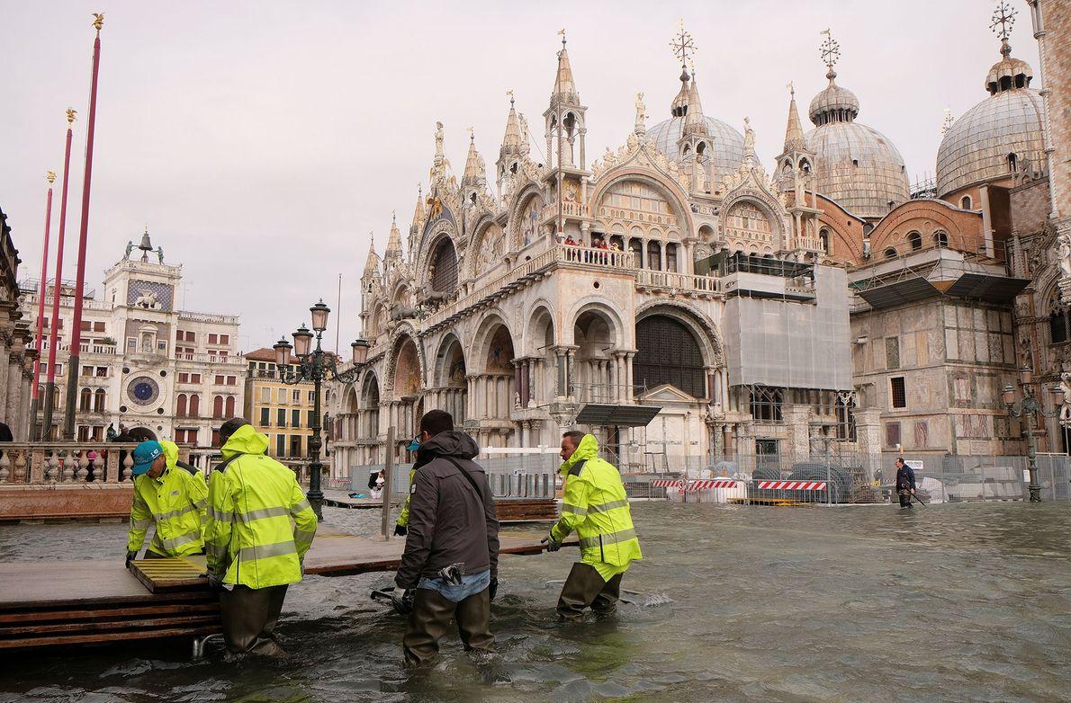Los trabajadores preparan una pasarela temporal en la plaza inundada de San Marcos.