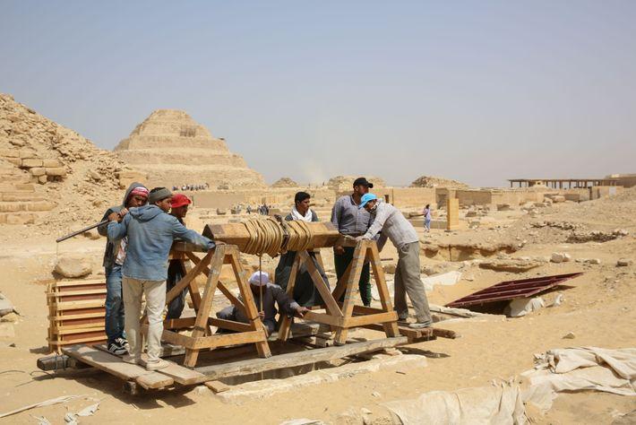 Los obreros usan un cabrestante con manivela para bajar las herramientasal taller de momias y las ...