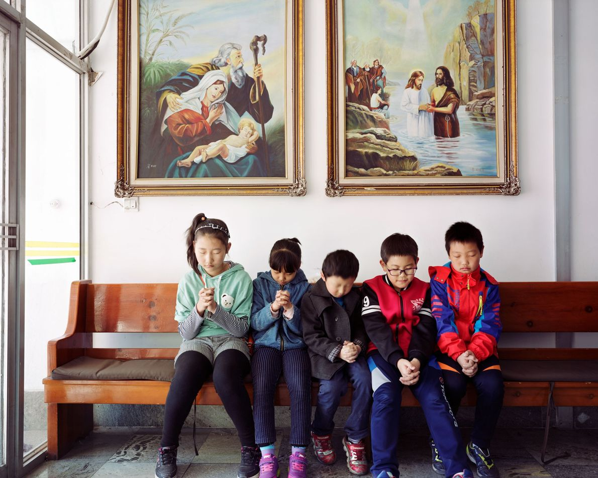 Cinco niños coreanos rezan en una iglesia local en Longjing, provincia de Jilin, China, 2017. Situada ...