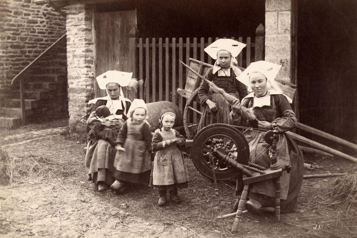 Las mujeres trabajan en las calles de Bretaña, Francia, hilando hilados sobre husos en 1914.