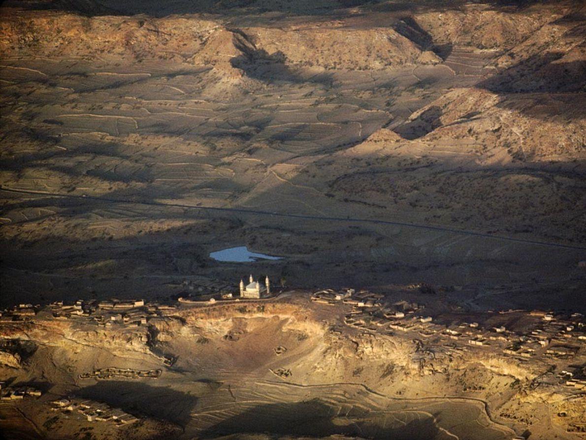 Una mezquita domina las aldeas agrícolas de Adi Caieh, Eritrea. Los escarpes, hoy gravemente erosionados, en ...