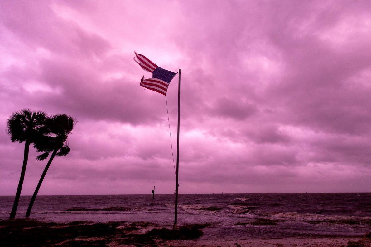 Una bandera estadounidense destrozada por el huracán Michael continúa flameando bajo la luz rosada del atardecer ...