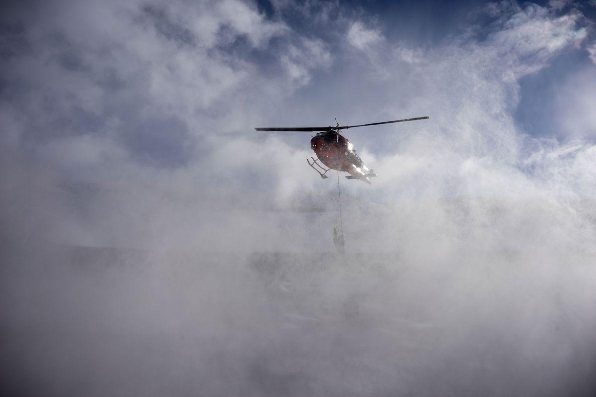 Un helicóptero deja caer una carga al equipo del campamento de Collinson Ridge. El equipo pasó ...