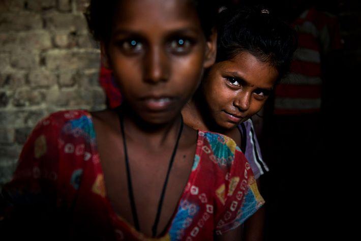 Chandni mira desde atrás de Kisna, ambas de 9 años de edad. Kisna ya está casada ...