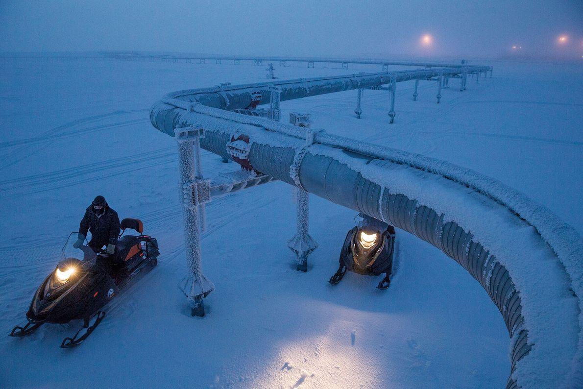 Trabajadores en un yacimiento de gas natural en Rusia inspeccionan las tuberías que envían gas a ...