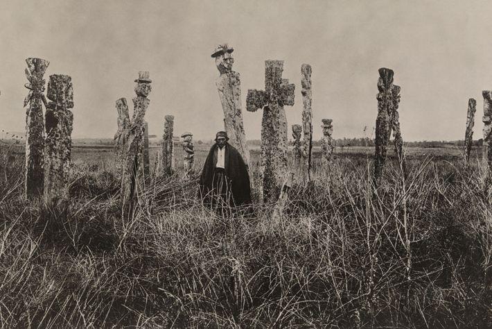 Un hombre araucano se encuentra en medio de un cementerio en Chile.