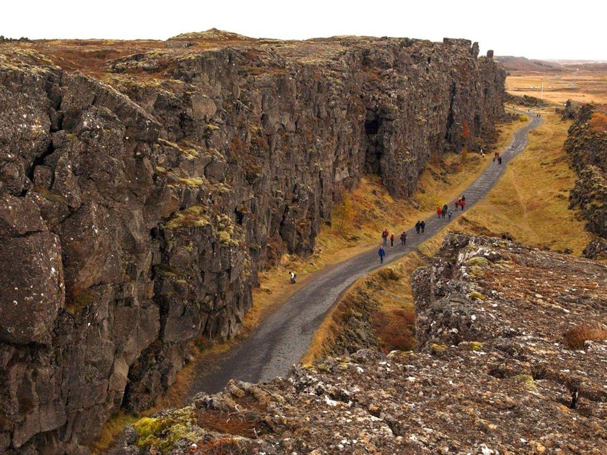 Los excursionistas caminan a la sombra de los acantilados en el Thingvellir National Park de Islandia. ...