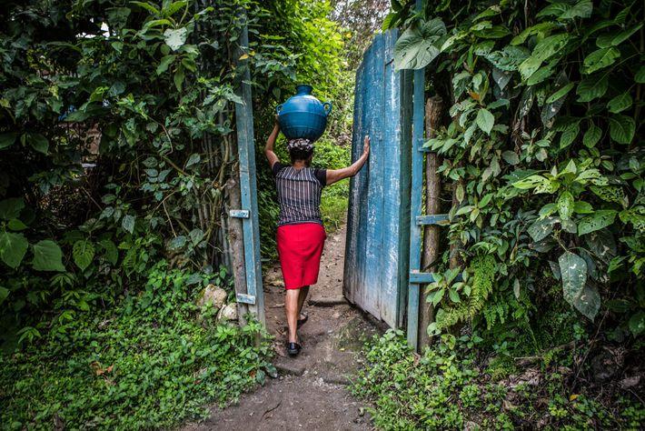 Zoila Ramírez, de 40 años, lleva una jarra de agua a su casa en San Jerónimo ...