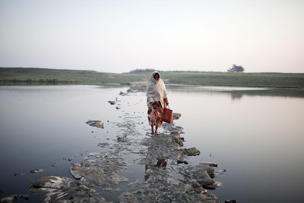 Una mujer cruza un pequeño canal del Ganges sobre un puente de basura sumergido en el ...