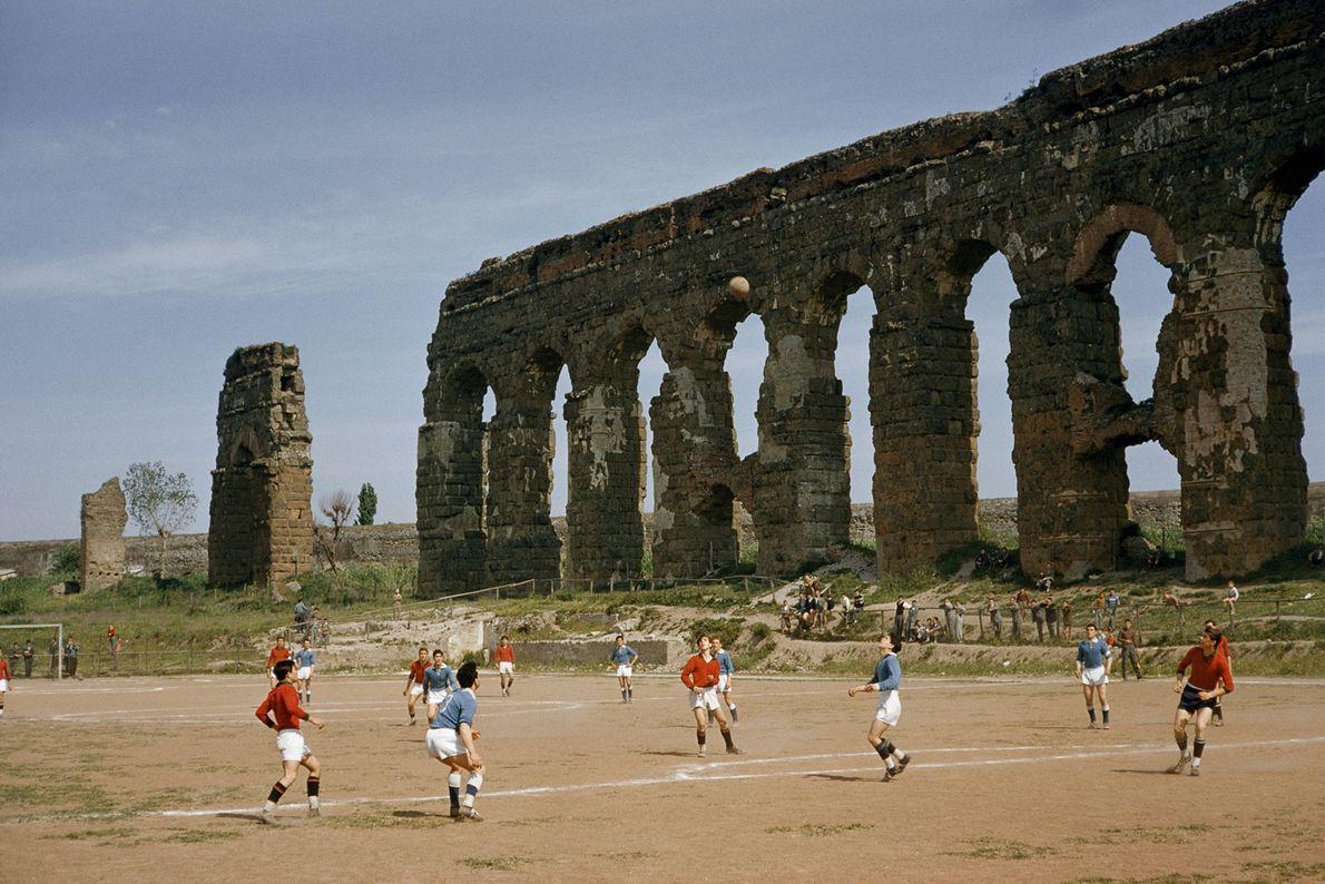 En 1957, unos niños juegan al fútbol al lado de los arcos de un acueducto en ...