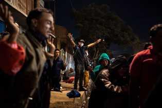 Mientras un pastor hondureño dirige la oración en un altavoz, los fieles cierran los ojos y ...